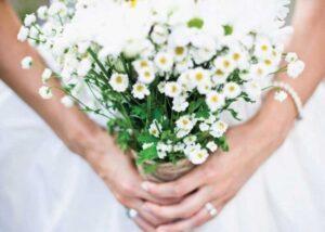 女性がマーガレットの花束を持っている写真